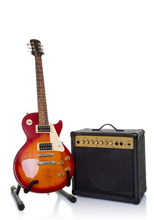 Red orange sunburst electric guitar and amplifier on white background