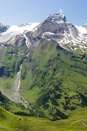 View of a meddow with a little cottage in the alps