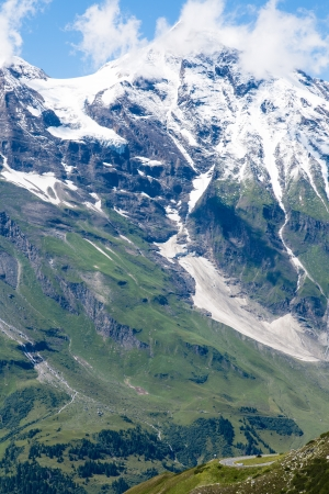 View over the Alps with a road and cars in the foreground Stock Photo