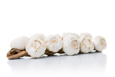 Garlics laying on a white table Stock Photo