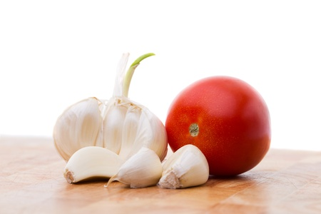 Tomato and peeled garlic on a cutting board Stock Photo