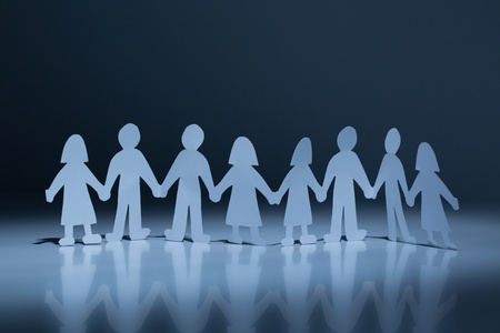 Chain of paper cut people in spotlight against a dark background photo