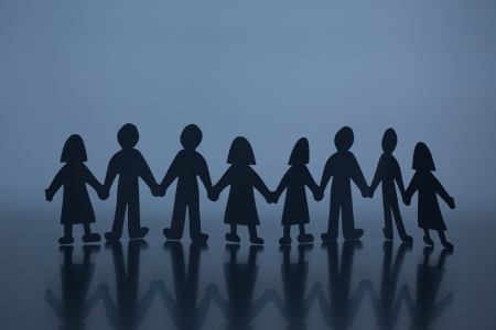 silhouette of chain of paper cut people Stock Photo