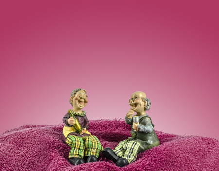 Two dolls which made like grand mom   grand dad sit on towel moutain photo