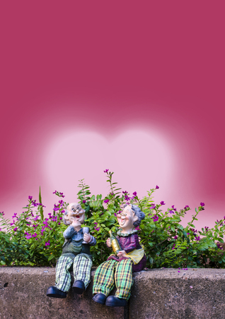 Two dolls which made like grand mom   grand dad sit on a brick wall infront of flowers and red heart back ground photo