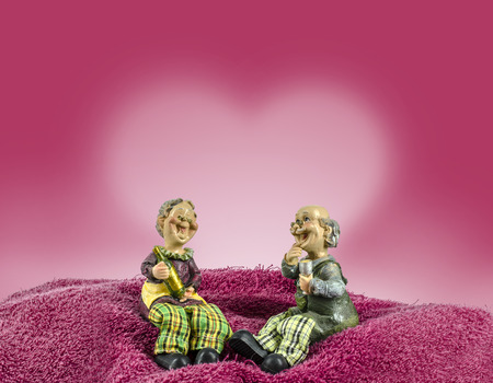 Two dolls which made like grand mom   grand dad sit on towel moutain have red heart back ground photo