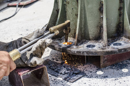making hole: A black smith is making hole on steel plate by using gas and fire