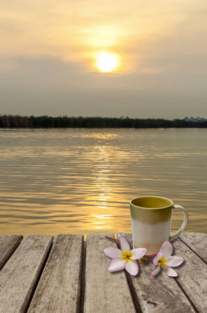 An image of coffee cup and flower on old wood table placed on the lake at sunset time Stock Photo