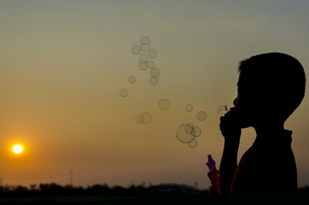 silhouette image of a boy blowing bubbles which have sunset sky as background photo