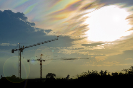 sillouette: Sillouette white lens flare image of tower crane which have rainbow sky as background