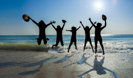 sillhuette Bild mit Lens Flare Effekt von 5 asain Mädchen springen auf dem Strand, die als Hintergrund blaue Meer und blauer Himmel haben