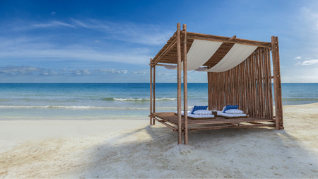 3D rendering image of bamboo tent which cover by fabric loacted on the beach,  fabric ceiling being blow by wind from the sea, white and blue day bed and pillow Stock Photo