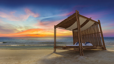 day bed: 3D rendering image of bamboo tent which cover by fabric loacted on the beach,  fabric ceiling being blow by wind from the sea, white and blue day bed and pillow,twilight time Stock Photo