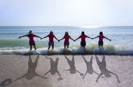 An image with lens flare effect of 5 asian girls standing with hand in hand on the beach which have blue sea and blue sky as background  but the shadow on the sand are jumping action