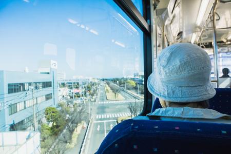 Ältere Frauen mit Hut im Zug starren auf die leere Straße