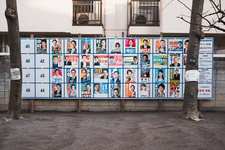 TOKYO,JAPAN MARCH 12 2019 Politicians on a political campaign poster at public playground Standard-Bild - 136011541