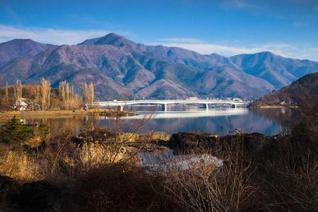 Kawaguchiko Ohashi bridge at Kawaguchi lake in March with dry grass forground and mountain background Фото со стока