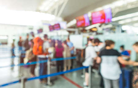 Blurred Airport Check-In Counters With Passengers And Crowd Control Barriers.Travel and transportation defocus background concepts.