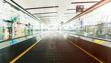 Empty travelator with morning light reflection in the air port terminal.passenger moving walkway. Travel and transportation concepts.