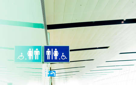 Toilet sign for Male, Female and Handicap with reflection and Public drinking water sign at the airport 免版税图像