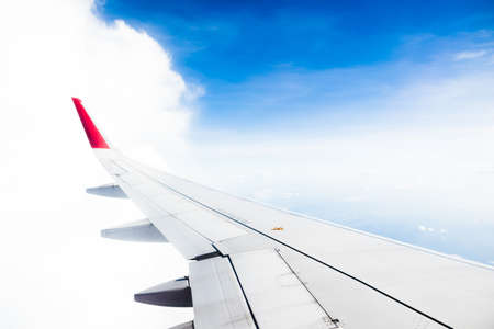 View from airplane on the aircraft white wing flying over blue sky and white clouds.Air travel and transportation concept.