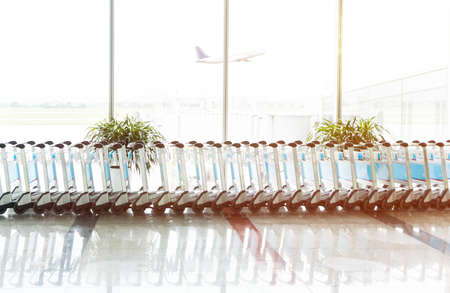 The row of empty luggage Trolley in the airport with an airplane taking off in the morning. Travel and transportation concepts.
