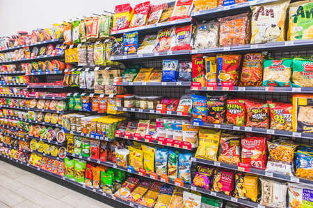 HANOI,VIETNAM - March 1,2021 -Many snack and candy brand sale on the shelf in a convenience store,Variety of snack, chips, cookies, crackers, sweet on Supermarket shelves background.