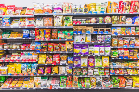 HANOI,VIETNAM - March 1,2021 -Variety of snack, chips, cookies, crackers, sweet on Supermarket shelves background, Many snack and candy brand sale on the shelf in a convenience store. Editorial