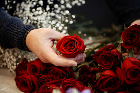 Happy caucasian florist making bouquets of red and pink roses for Valentine's day. Concept of human emotions, facial expression, love, and hard work in this pandemic times. Standard-Bild