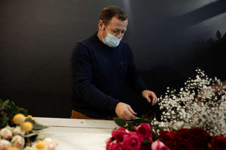Happy caucasian florist making bouquets of red and pink roses for Valentine's day. Concept of human emotions, facial expression, love, and hard work in this pandemic times.