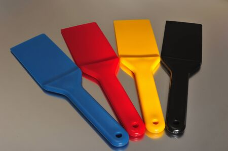 4 color printing: Spatulas to spread the ink used in offset printing Stock Photo