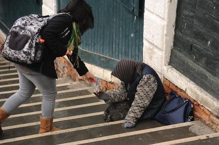 generosidad: turista que le da dinero a un mendigo Foto de archivo