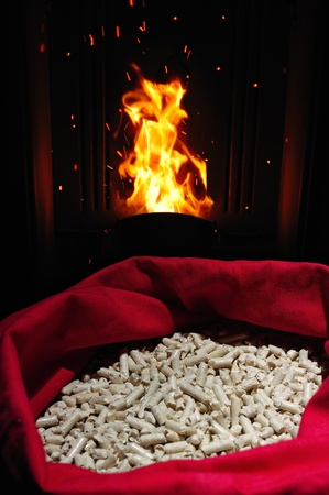 bioenergy: wood pellets in canvas sack, with stove and flame
