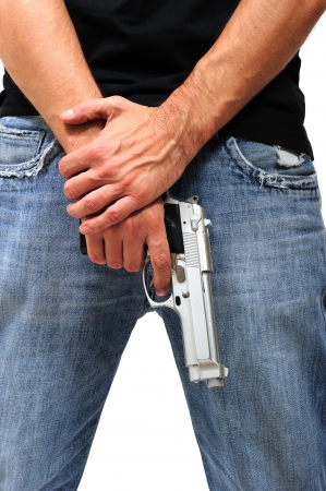 Man holding a gun facing the ground, isolated on white photo