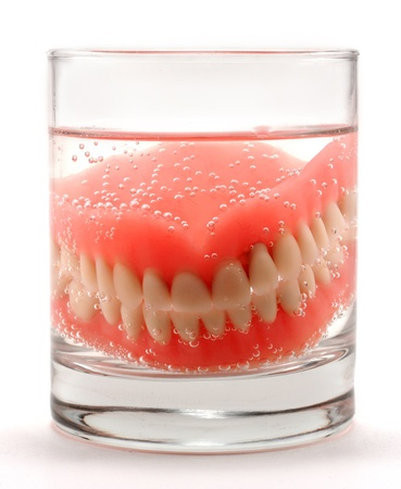 Dentures placed in a glass of water for cleaning