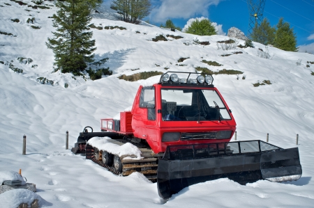 snowcat: red snowplow parked in the snow