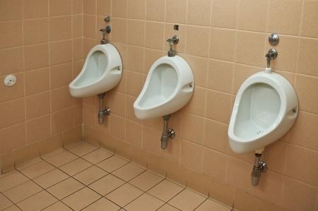 flushing: Three men urinals in the public restroom Stock Photo