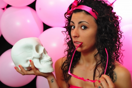 gruesome: girl in pink with a white skull in his hand