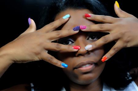 modelos negras: Primer plano de una joven mujer de negro con las uñas pintadas