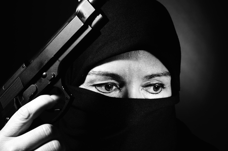 close-up of veiled middle eastern woman  with gun photo