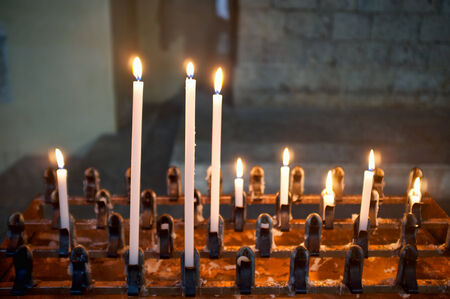 homily: lighted candles in an old church Stock Photo