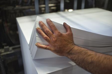 imprenta: primer plano de la carga manual de papel offset m�quina de impresi�n