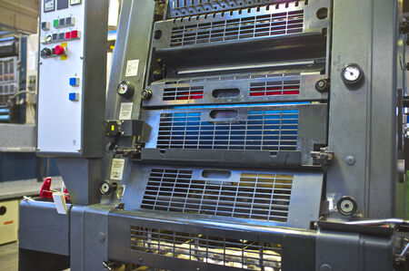 manually: close-up of manually loading paper offset printing machine