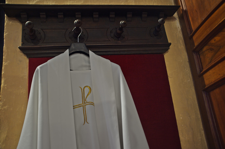 priest's ritual robes: white vestment for priest, hanging on the hanger