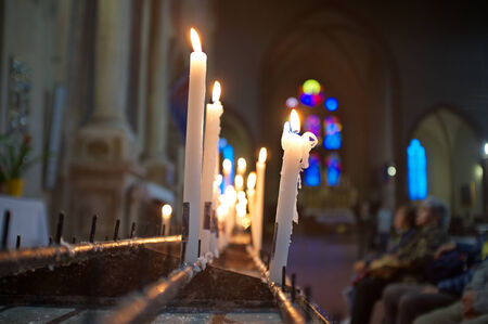 sacraments: lighted candles in an old church, with people praying Stock Photo