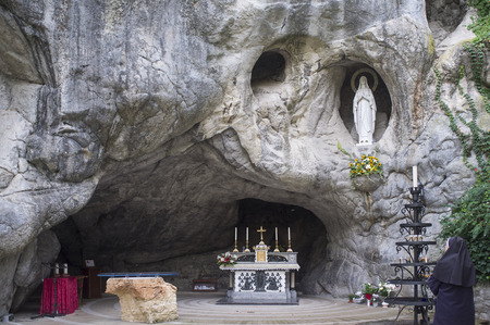 sanctuary of Chiampo, reproduction of Lourdes grotto in France, with nun praying 版權商用圖片