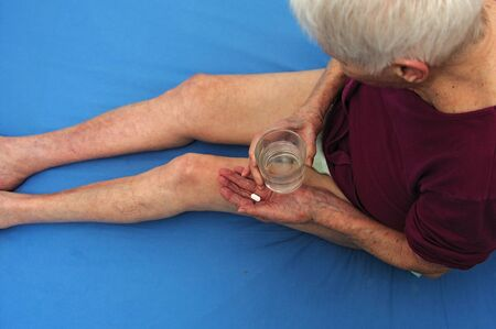 incontinence: caucasian old woman is lying in bed and taking pill