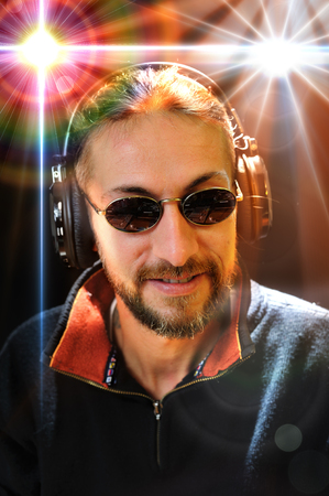 deejay: happy deejay whit sunglasses wearing headphones during party at the disco