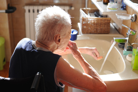 debility: senior lady in wheelchair that washes and wears the dentures in the bathroom