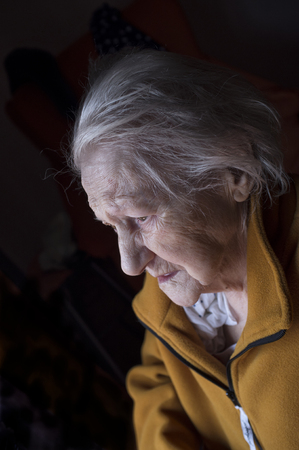 debility: portrait of sad lonely pensive old senior woman looking in a window Stock Photo